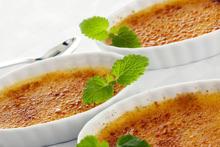 tilted view: three bowls of creme brulee garnished with mint leaves, tilted view, closeup