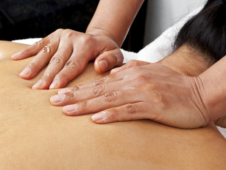 hands of massage therapist pressing womans back photo