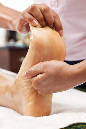 massage therapist kneading a female foot photo
