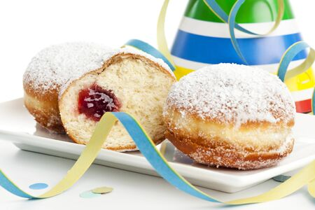 hat new year s eve: two and a half bismarck donuts on a plate surrounded by party decoration Stock Photo