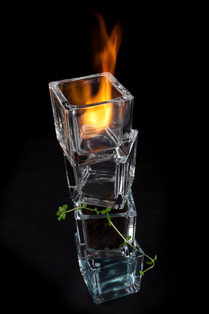 The four elements - Fire, Water, Earth and Air - symobolized by stacked small glass containers holding a flame, nothing, a small sprout in soil and blue tinted liquid Stock Photo - 29455146