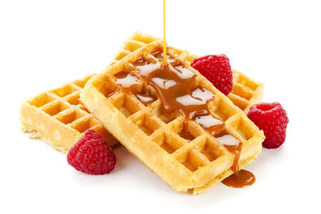 caramel sauce flowing over a heap of belgian waffles decorated with raspberries, isolated on white background photo