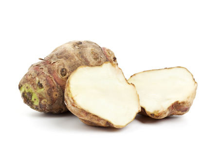 topinambur roots, also called Jerusalem artichokes, whole fruit and two halves, isolated on white Standard-Bild