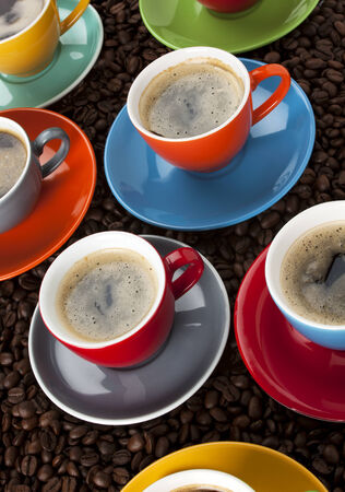 tilted view: various cups of espresso in colorful cups upon coffee beans, tilted view