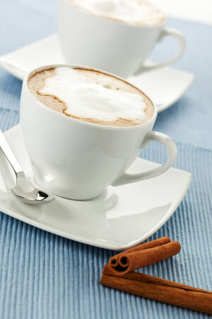 tilted view: two cups of cappuccino or latte macchiato, cinamon sticks in foreground, tilted view Stock Photo