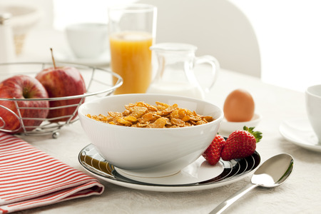 healthy breakfast with cereal flakes, apples, orange juice photo