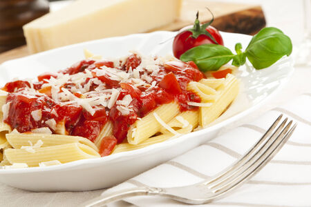 tilted view: penne with tomato sauce and grated cheese, garnished with tomato and basil leaves, tilted view