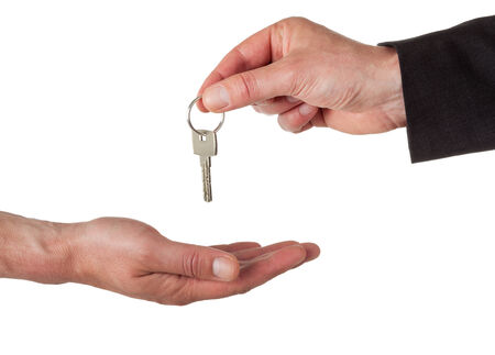 hand of business man giving key into another hand photo