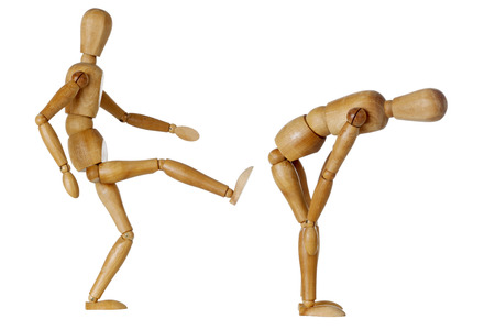 wooden mannequin kicking butt of another one bending down Stockfoto