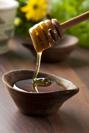 honey flowing from drizzler into small wooden bowl, flower in background