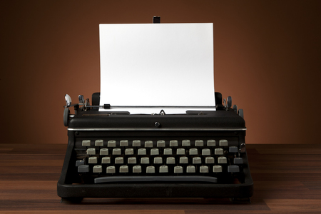 old portable typewriter with blank paper on desk photo