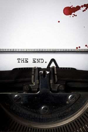 Words The End written on old typewriter, closeup, blood stains on paper photo