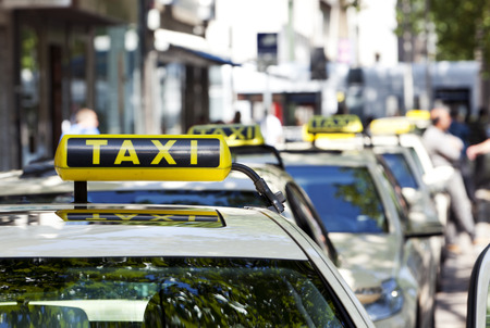 german taxi cabs waiting in line, focus on sign on first car Standard-Bild