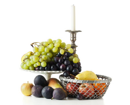 variety of fruit in basket and bowl, with candleholder, isolated on white background photo