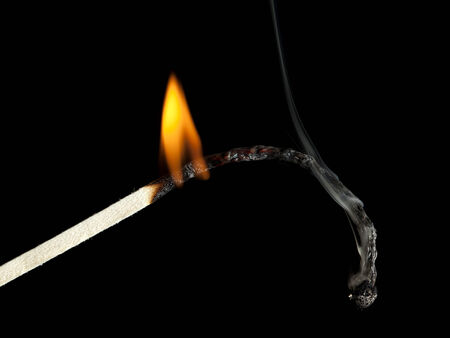 macro of burning match, slowly extinguishing, black background. Metaphor for death and exhaustion Stock Photo