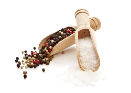 rough salt and mixed peppercorns on wooden shovels, isolated on white