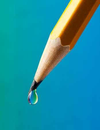 writing utensil: Water drop with rainbow colored refraction clinging on the tip of a pencil Stock Photo