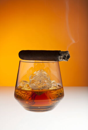 unhealthy living: Smoking cigar on top of tumbler filled with whisky on the rocks