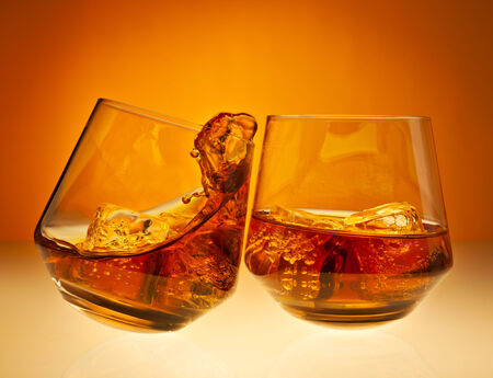 Two glasses with whisky on the rocks clicking together, one spilling over