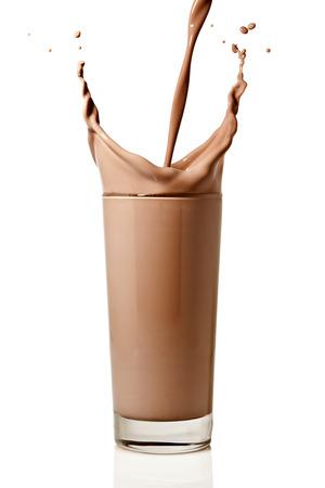 Schokoladenmilch oder Proteinshake in ein Glas fließt, macht einen großen Sprung, isoliert auf weißem Hintergrund