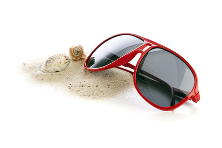 Red sunglasses on heap of sand with shell and seasnail isolated photo