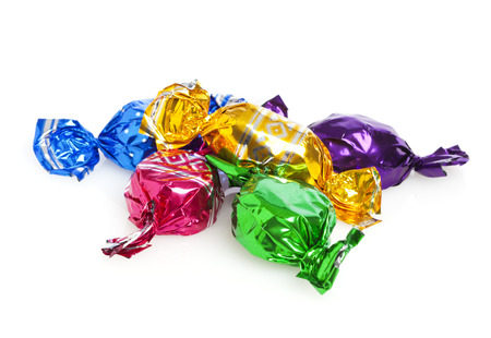 wrapped: Five candies wrapped in colored foil on white background Stock Photo