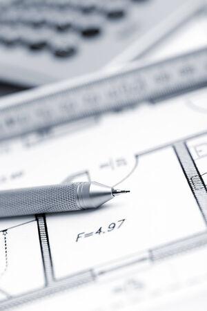 yardstick: architect s pencil, yardstick and calculator on floor plan, selective focus