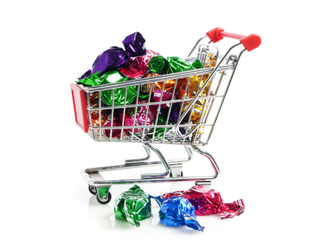 shopping binge: hard candy in colorful wrappers in shopping cart, isolated on white background