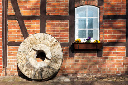 millstone: Old millstone standing in front of half-timbered building