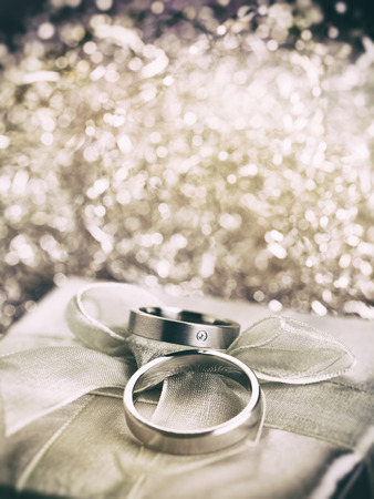 Wedding rings on gift box with bow, bokeh in background, vintage processing photo