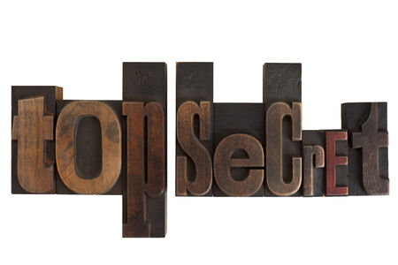phrase top secret in vintage wooden letterpress type, scratched and stained, isolated on white background photo