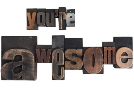 phrase youre awesome in vintage wooden letterpress type, scratched and stained, isolated on white background photo