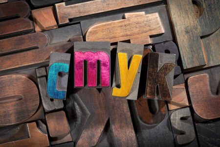 cmyk written with colored vintage letterpress printing blocks on random letters background photo