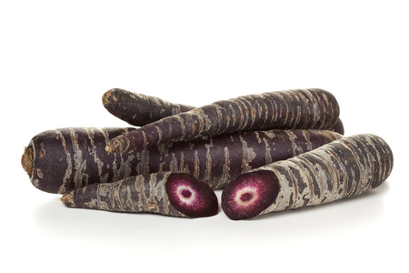 Heap of purple carrots isolated on white background, one cut through