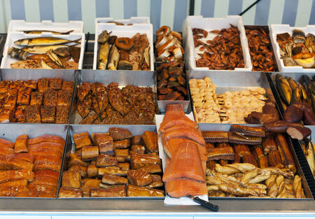 Variety of fresh and prepared fish presented at market stand photo