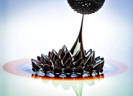 Macro photograph of Ferrofluid flowing from one magnet to another. Ferrofluid is a colloidal liquid of nanoscale particles in a carrier fluid that becomes magnetized by approaching a magnet. photo