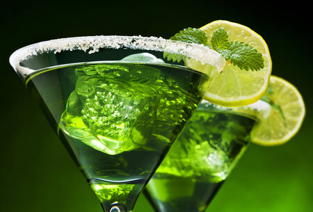 Closeup of green cocktails in martini glasses with ice cubes, lime slices, mint leaves and sugared edge photo