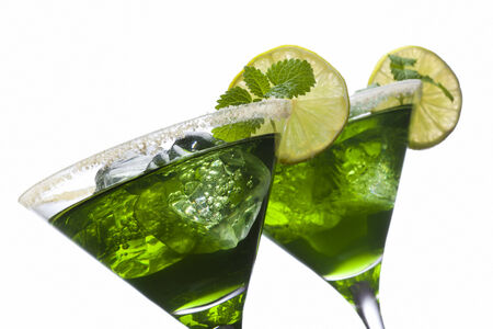 tilted view: Green cocktails in glasses with sugared edges, lime slices, mint leaves and ice cubes isolated on whitre, tilted view Stock Photo