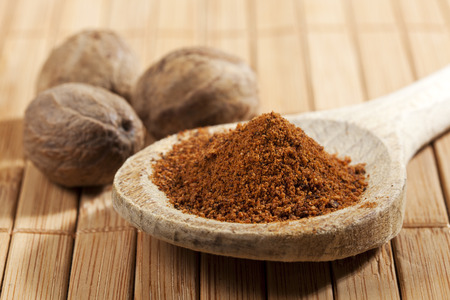 Nutmeg, whole nuts behind wooden spoon with a heap of powder