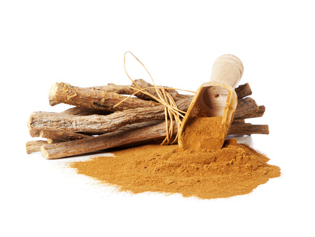 liquorice: Pile of ground liquorice with wooden shoverl and native liquorice sticks (Glycyrrhiza acanthocarpa)
