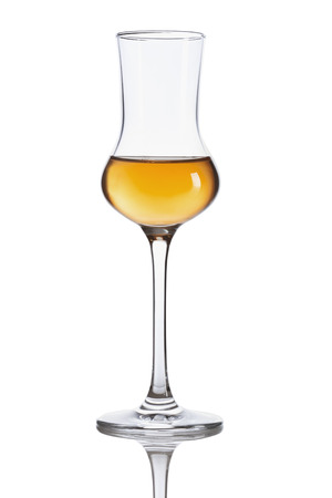 Glass of dark italian Grappa brandy isolated on white background