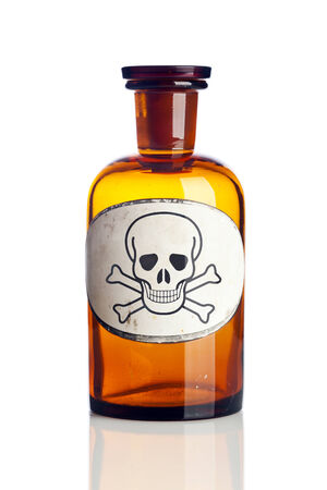Old pharmacy bottle with skull and bones warning label isolated photo