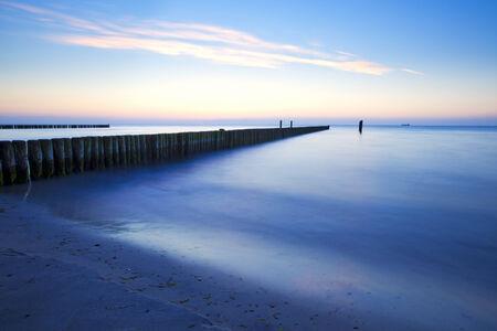 breakwaters: Sunset at Baltic Sea beach with breakwaters, long exposure Stock Photo