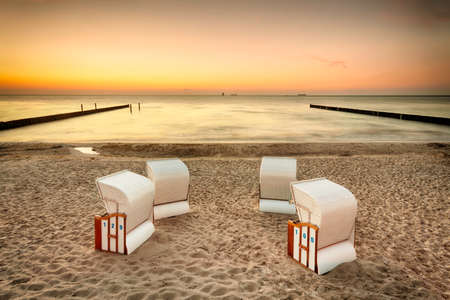 Four beach chairs on baltic sea beach at sunset, lomg exposure HDR image photo