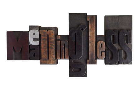 meaningless: Word meaningless in vintage wooden letterpress type, scratched and stained, isolated on white background Stock Photo