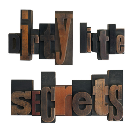 ittle: phrase dirty little secrets in vintage wooden letterpress type, scratched and stained, isolated on white background