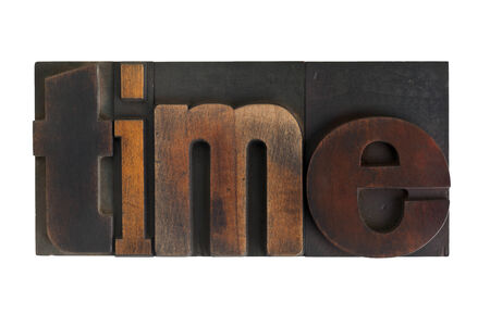word time written in vintage wooden letterpress type, scratched and stained, isolated on white photo