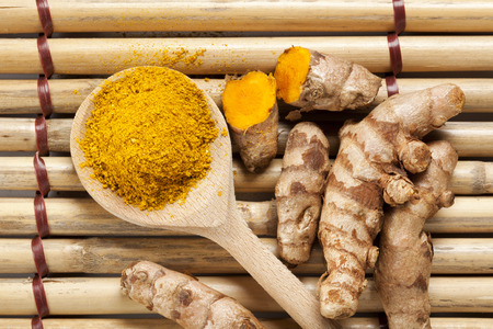 Ground turmeric on wooden spoon and rhizomes on bamboo mat, from above Stockfoto