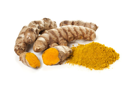 Ground turmeric and turmeric roots isolated on white background