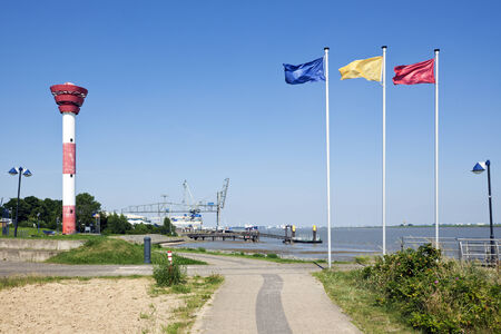 flagpoles: Lighthouse and piers at Nordenham, flagpoles with flags in foregropund Stock Photo